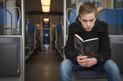 Jongen leest in de trein